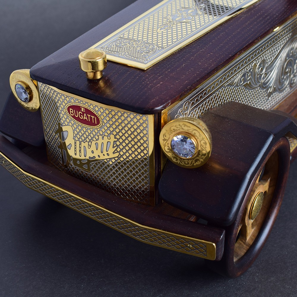 Jewelry model of a car brand Bugatti. In retro headlights inlaid with transparent crystals. The radiator grill is cut out under a microscope and coated with gold. A luxurious gift for a collector or business person