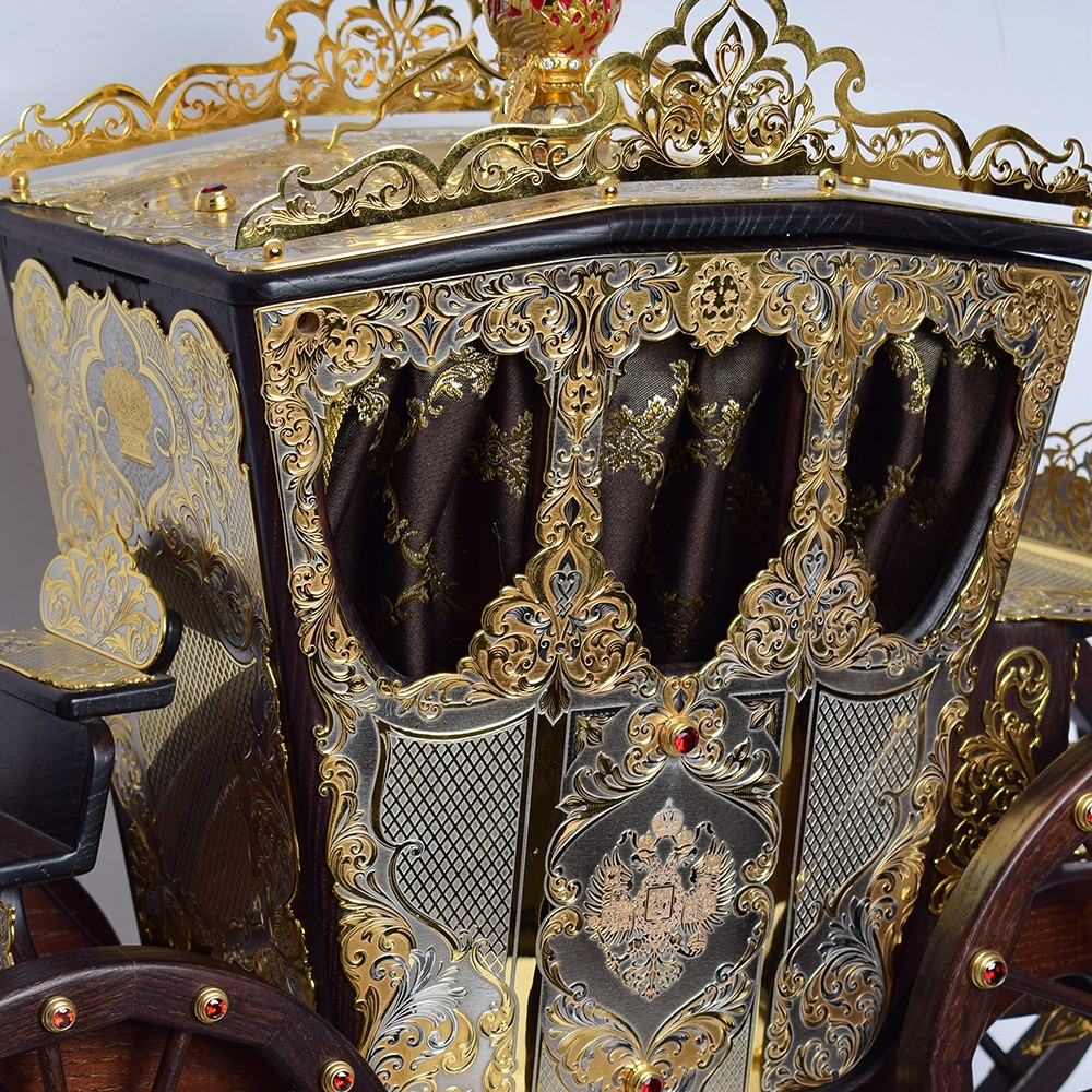 A large wooden carriage decorated with decorative slips. The surface of the linings is decorated with relief engraving and gilding.