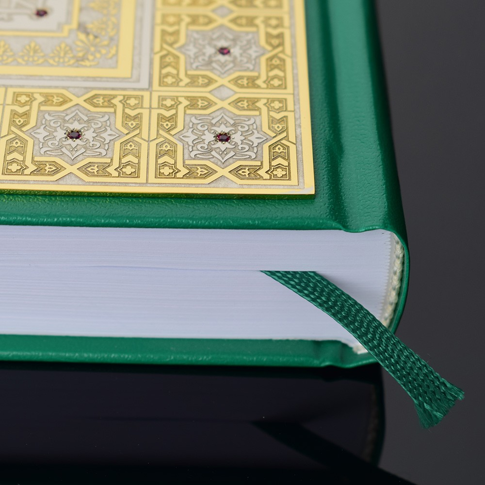Green Quran decorated with a gold overlay